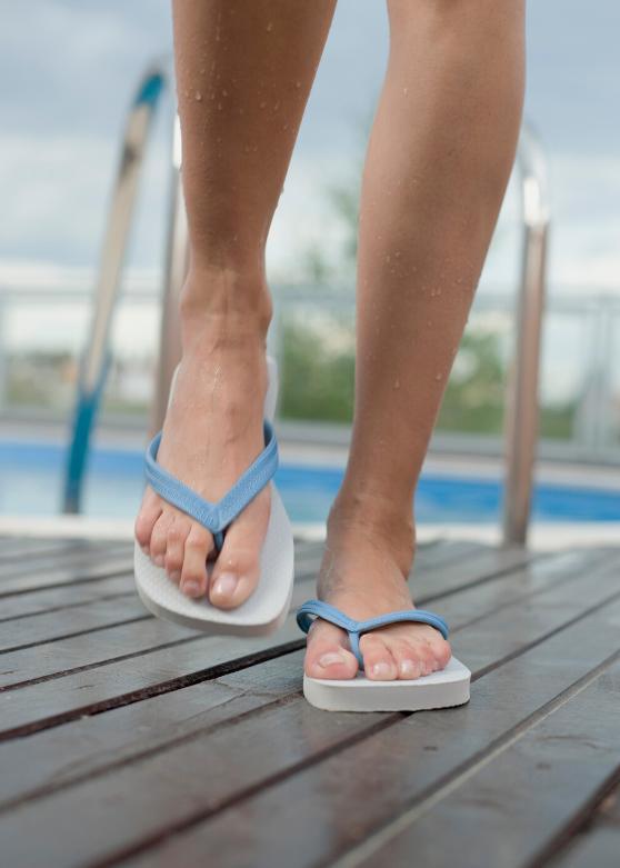 Feet Walking in Flip Flops on the Pool Deck